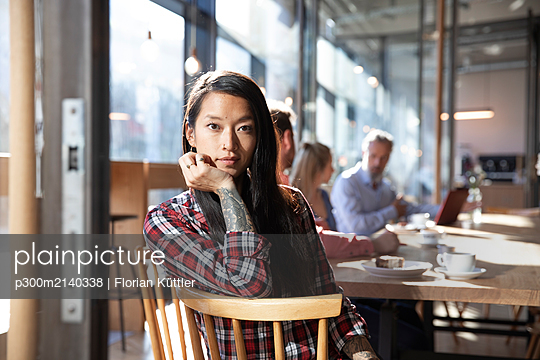 Portrait of woman with colleagues in a cafe - p300m2140338 by Florian Küttler