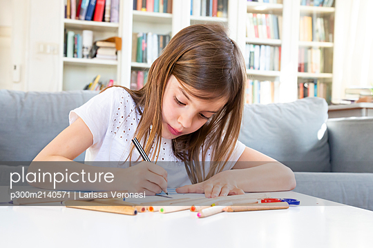 Portrait of girl drawing with coloured pencil at home - p300m2140571 by Larissa Veronesi