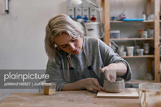 Young woman working on workpiece in pottery - p300m2166527 by Juri Pozzi