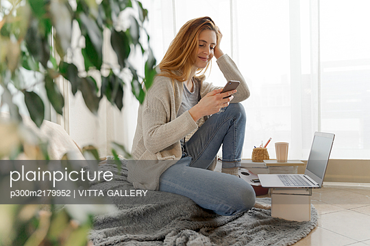 Young woman using smartphone at home - p300m2179952 by VITTA GALLERY