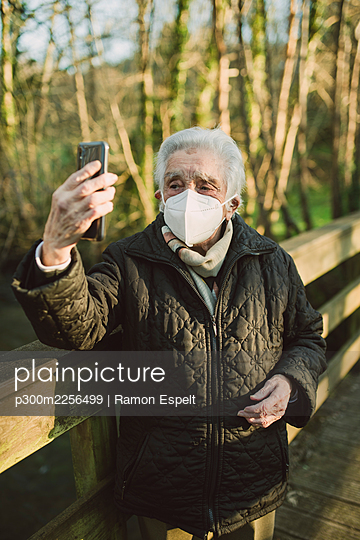 Elderly woman taking selfie through mobile phone while standing on footbridge during COVID-19 - p300m2256499 by Ramon Espelt