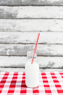 Close-up of milk bottle with striped straw on tablecloth - p1094m1015328 by Patrick Strattner