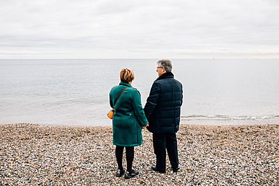 Rear view of an older couple by the sea - p1166m2078396 by Cavan Images