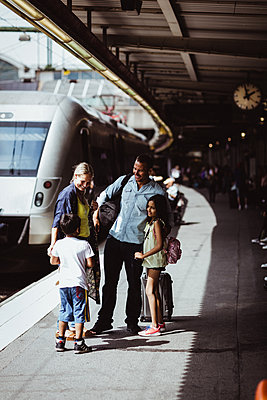 Family greeting man at railroad station - p426m2146134 by Maskot