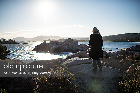 Woman walking on stones along the sea - p1007m1540373 by Tilby Vattard