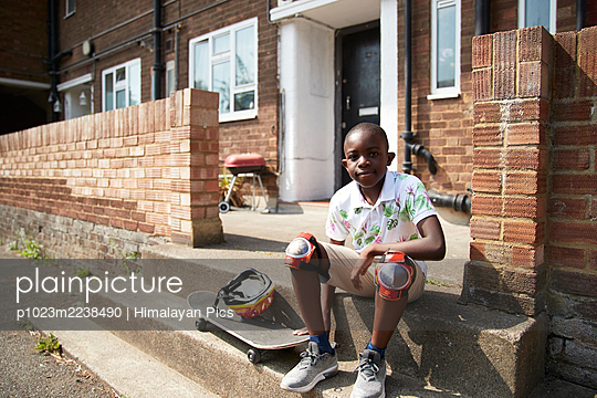 Portrait confident boy with skateboard on sunny front stoop - p1023m2238490 by Himalayan Pics