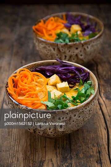 Turmeric curry dish with carrot, tofu, red cabbage and parsley in bowl - p300m1563152 by Larissa Veronesi