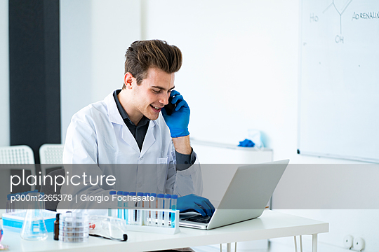 Male scientist talking on smart phone while using laptop at desk in laboratory - p300m2265378 by Giorgio Fochesato