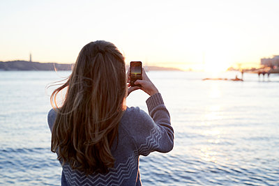 Woman taking a picture of sunset - p1124m1564690 by Willing-Holtz