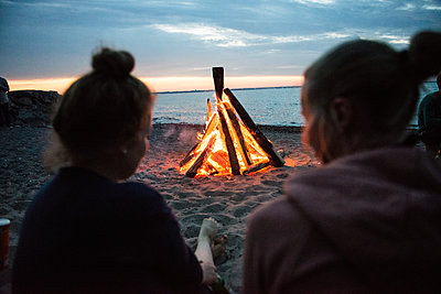 Freundinnen sitzen am Lagerfeuer am Strand - p1142m1362247 von Runar Lind