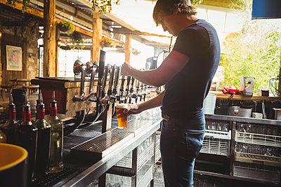 Bar tender filling beer from bar pump - p1315m1198787 by Wavebreak