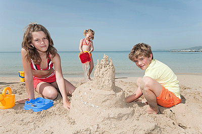 Spain, Mallorca, Children building sandcastle on beach - p3008874f by Westend61