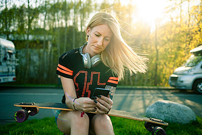 Portrait of blond woman with longboard sitting at roadside using smartphone - p300m1586965 von sinanmuslu