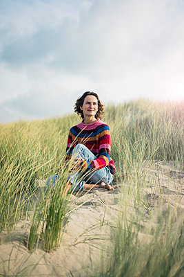 Mature woman relaxing on the beach, sitting in the dunes - p300m2059465 by Robijn Page