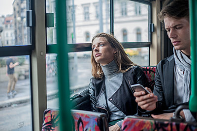Thoughtful woman sitting with male colleague using smart phone in bus - p300m2240027 by LOUIS CHRISTIAN
