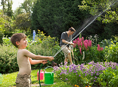 A boy squirting a hose in a garden - p30117764f by Jutta Klee photography
