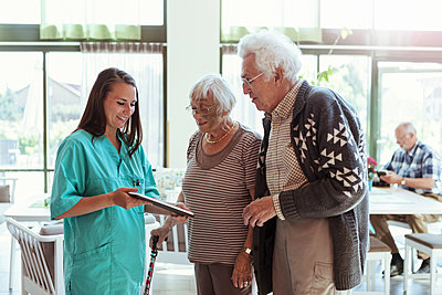 Young caretaker showing digital tablet to senior couple at nursing home - p426m2072558 by Kentaroo Tryman