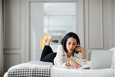 Businesswoman using smartphone and laptop in suite - p429m2058381 by Sofie Delauw