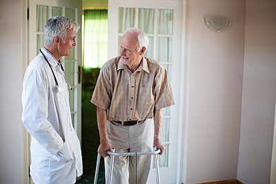 Doctor talking to patient using walker - p555m1305747 by Resolution Productions