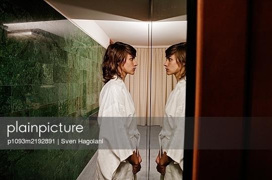 Junge Frau vor einem Spiegel, Portrait - p1093m2192891 von Sven Hagolani