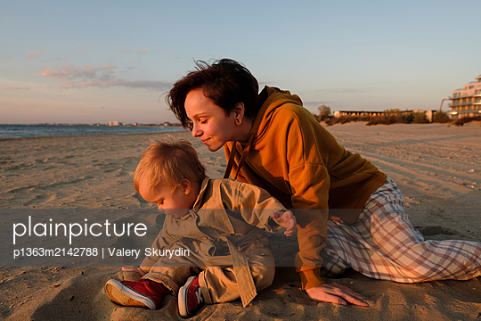 Woman with baby playing on beach - p1363m2142788 by Valery Skurydin