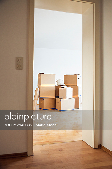 Cardboard boxes in an empty room in a new home - p300m2140895 by Maria Maar