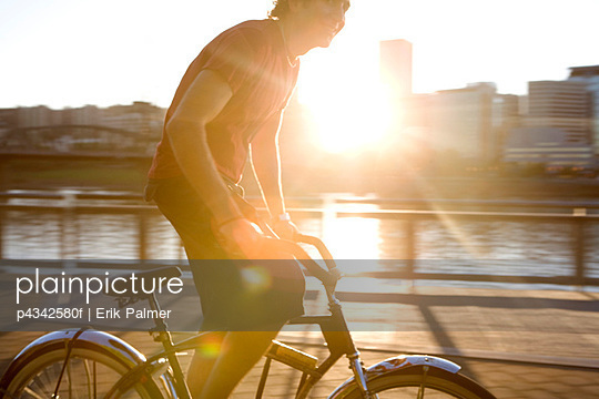 Athletic man riding bicycle on urban bridge at sunset