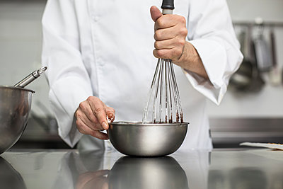 Chef whipping cream with whisk in bowl - p1166m2130282 by Cavan Images