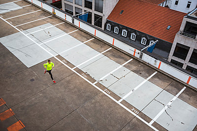 Young man running on parking level - p300m1449416 by Daniel Ingold