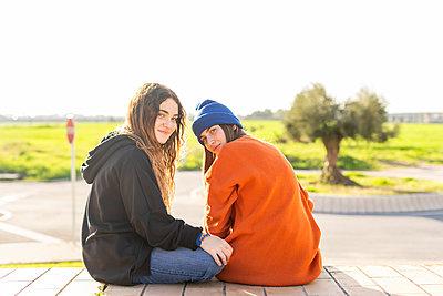 Portrait of two teenage girls sitting  outdoors - p300m2170153 by Eloisa Ramos