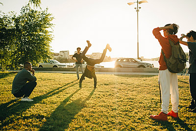 Friends watching teenage boy doing handstand on field during sunny day - p426m2075171 by Maskot