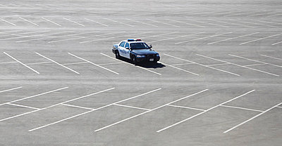 Police car parked in empty lot - p429m817497 by Robin James
