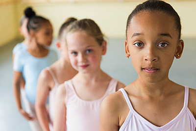 Girls standing in a row in ballet studio - p555m1491096 by Mark Edward Atkinson