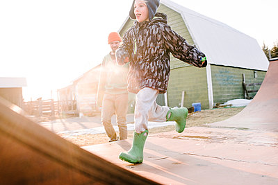 Boy with father running on sunlit farmyard skateboard ramp - p924m2097752 by Viara Mileva