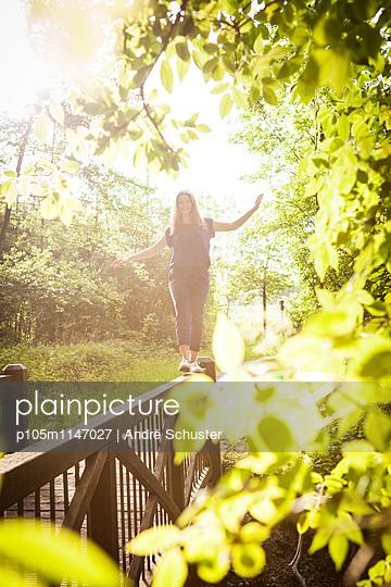 Junge Frau balanciert auf einem Geländer  - p105m1147027 von André Schuster