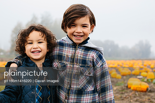 Portrait of happy brothers standing at pumpkin patch during foggy weather - p1166m1416220 by Cavan Images