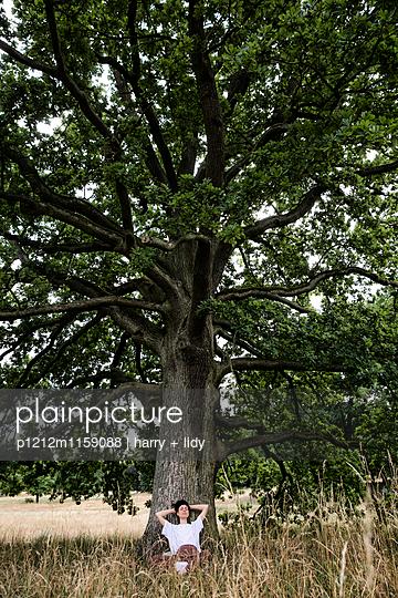 Junge Frau sitzt unter einem Baum - ausruhen - p1212m1159088 von harry + lidy