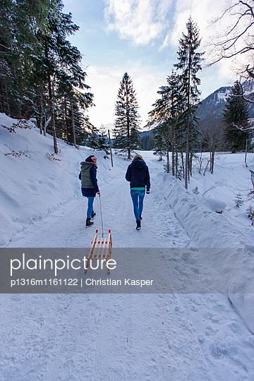 Zwei Frauen mit einem Schlitten, Spitzingsee, Oberbayern, Bayern, Deutschland - p1316m1161122 von Christian Kasper