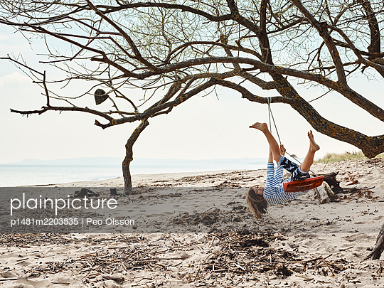 Girl playing on swing on sandy beach, Sweden - p1481m2203835 by Peo Olsson