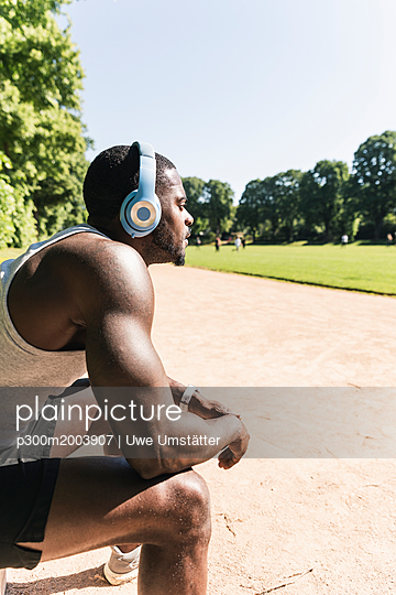 Smiling young athlete taking a break, wearing headphones, listening music - p300m2003907 von Uwe Umstätter