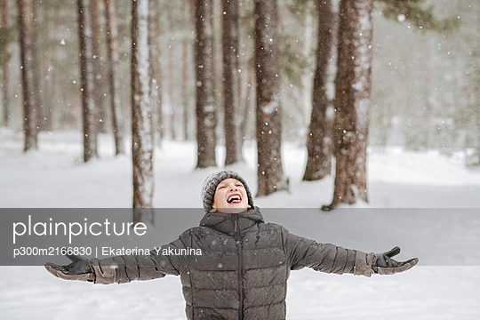 Portrait of boy catching snowflakes in winter forest - p300m2166830 by Ekaterina Yakunina
