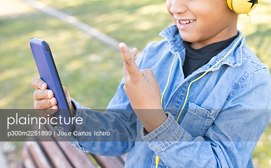 Boy showing peace gesture while using mobile phone at park - p300m2251899 by Jose Carlos Ichiro