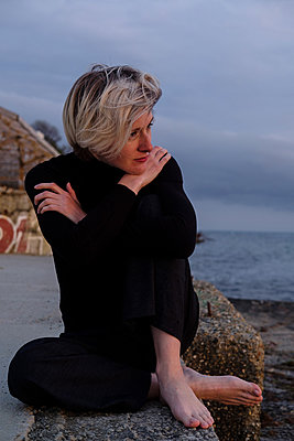 Woman sitting near sea - p1363m2108777 by Valery Skurydin