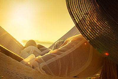 Woman wearing hat on hammock at sunset - p1427m2163625 by ac productions