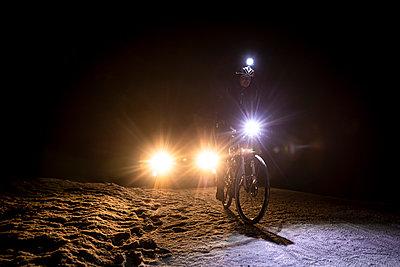 Cyclist followed by car at night in winter - p1687m2278812 by Katja Kircher