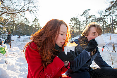 Girlfriend with boyfriend enjoying coffee during winter - p300m2287655 by Frank van Delft