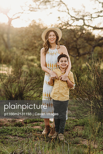 Full length portrait of young woman and son in backlit meadow - p1166m2131193 by Cavan Images