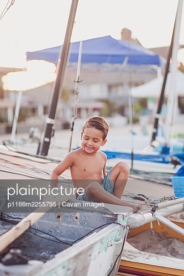 Young smiling boy sitting on a docked boat at the beach. - p1166m2255795 by Cavan Images