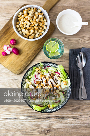 Bowl of Caesar salad with meat and red radish - p300m2023607 von Giorgio Fochesato
