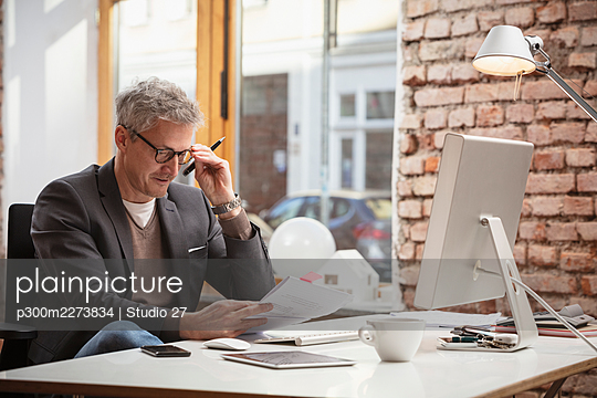 Male professional working on paper document while sitting at desk in office - p300m2273834 by Studio 27